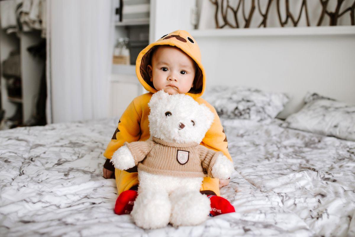 Kind auf Bett mit Kuscheltier